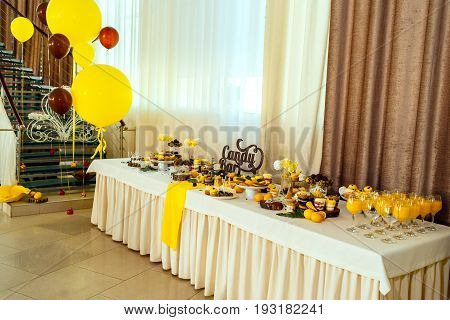 Holiday Candy Bar In Yellow And Brown Color. Wedding Candy Bar Served With Cupcakes, Cake Pops, Dess