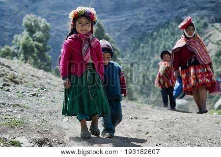 Native Peruvian girl and her little brother dressed in colourful traditional handmade outfit. October 21 2012 - Patachancha, Cuzco, Peru