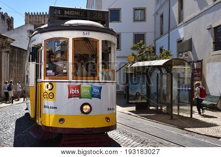 Yellow Tram On A Narrow Street In Lisbon, Portugal