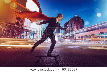 Young confident super businessman in red cape and black suit on a skateboard going fast . night scene with modern city .
