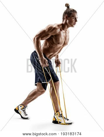 Side view. Sporty man performs exercises using a resistance band. Photo of strong male shirtless isolated on white background. Strength and motivation.