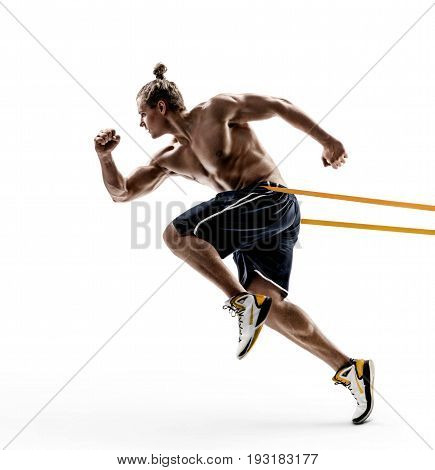 Sporty man runner in silhouette using a resistance band in his exercise routine. Photo of shirtless young male isolated on white background. Dynamic movement. Side view