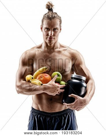 Resting time. Handsome muscular man holding fresh fruits and large bank of sports nutrition isolated on white background. Organic food and health concept
