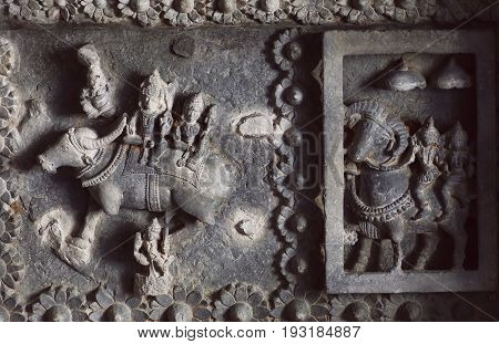Shiva Lord and his wife Parvati on carved wall of 12th century temple Hoysaleswara with ancient examples of indian architecture.