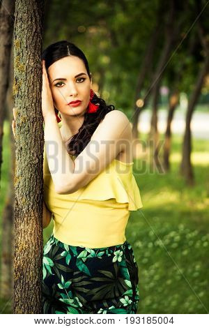 attractive dark hair woman portrait by the tree latino look with red lipstic and red striking earrings wearing yellow asymmetrical summer shirt