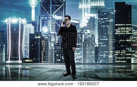 Happy smiling businessman using smartphone blurred morden city skyline .
