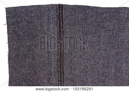Piece of dark blue jeans fabric isolated on white background. Rough uneven edges. Wrong side of fabric