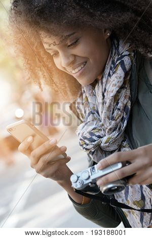 Woman photographer transfering files from camera to smartphone