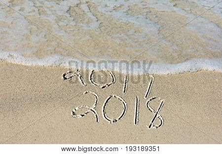 New Year 2018 text in beach sand with frothy surf water
