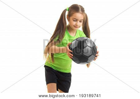cutie little girl in green uniform with soccer ball in hands isolated on white background