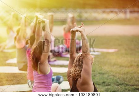 Group of women practicing yoga together during a beautiful sunny day on the meadow. Yoga in nature. Concept healthy
