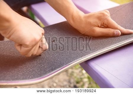 A young boy on his knees glues the griptape on a skateboard in the company of friends in sunny weather. Preparing a skateboard for a skatepark competition in the open air