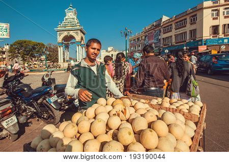 MYSORE, INDIA - FEB 18, 2017: Fruits and vegetables seller waiting for the customers and trading melons on street market on February 18, 2017. Mysore of Karnataka has a population of 900000