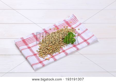 pile of peeled brown lentils on checkered dishtowel