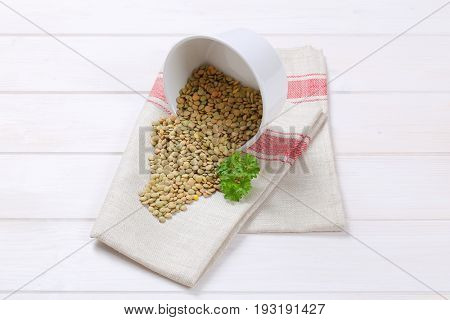 bowl of peeled brown lentils spilt out on white dishtowel