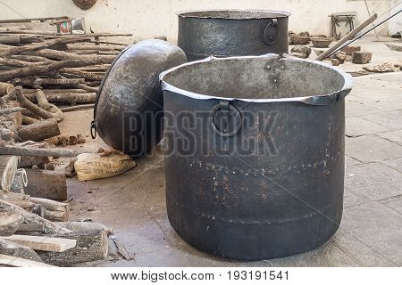Large pans for cooking the food for pilgrims. Old pots smoked with fire in the hindu temple near the wood on the floor