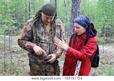 Scientists in the forest remove the data coordinates for GPS Navigator