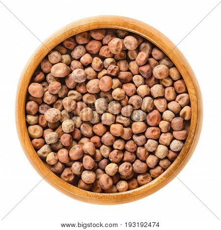 Dried snow pea seeds in wooden bowl. Light brown spherical seeds from the pods of Pisum sativum saccharatum, a legume and variety of pea. Isolated macro photo closeup from above on white background.
