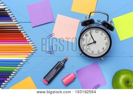 Wooden desk with stationery and empty stickers Alarm clock and apple.