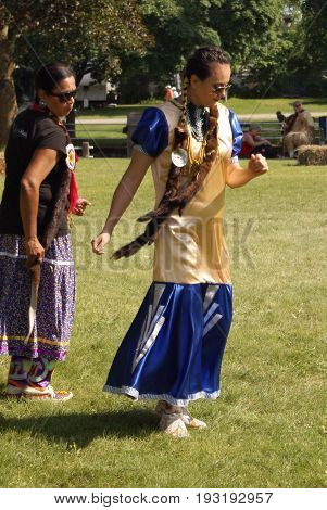 SMITHS FALLS ON JUNE 10 2017 EDITORIAL IMAGE SERIES OF NATIVES POWWOW CEREMONY with this image focused on a couple beautiful woman taken to the dance floor.
