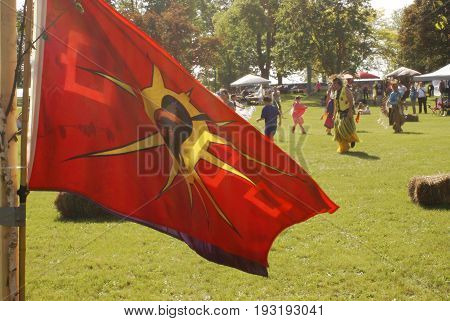 SMITHS FALLS ON JUNE 10 2017 EDITORIAL IMAGE SERIES OF NATIVES POWWOW CEREMONY with this image focused on the cultural flag and the festivities behind.