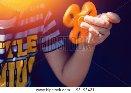 Child boy to play with Fidget Spinner in his hands, the concept of relieving stress, develop a small hand mathematics.