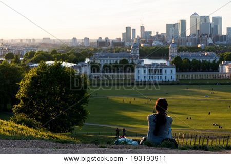 Woman sitting on the ground on the top of the hill at Greenwich Park, London and watching the sunset