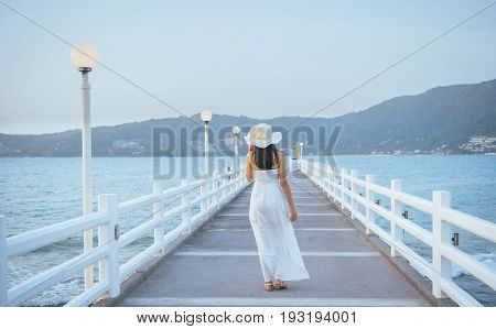 Pretty woman enjoy view of beautiful tropical beach in twilight time at Patong beach in Phuket province The most famous tourist attraction in Phuket province Thailand.