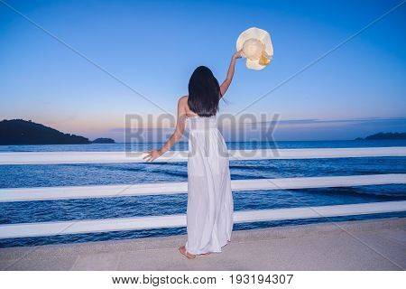 Pretty woman enjoy view of beautiful sunset sky on tropical beach in twilight time at Patong beach in Phuket province The most famous tourist attraction in Phuket province Thailand.