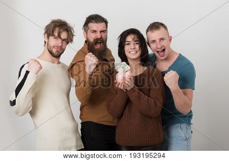 Happy Friends Putting Dollars In Piggy Bank With Winning Fists