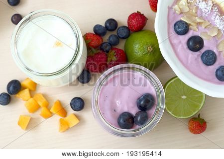 Fresh yogurt puddings with blueberries, mango or strawberries