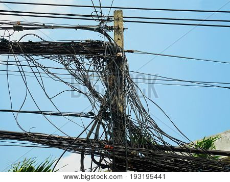 Utility pole supporting messy wires for various public utilities