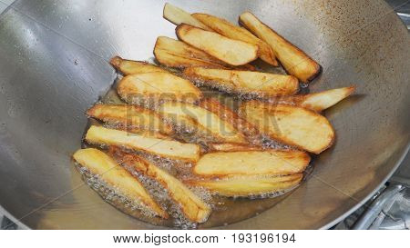 French fries potato snacks cooking with palm oil in stainless steel pan is scorch for finish.