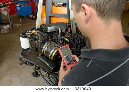 a mechanic man with digital multimeter testing ignition coil