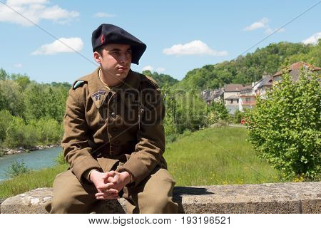 a french soldier in 1940's uniform sitting outdoor