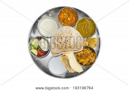 Traditional indian lunch with various foods. Typical meal served in restaurant on steel metal plate thali, isolated