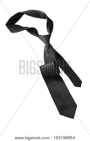 Elegant black silk necktie crumpled on white background