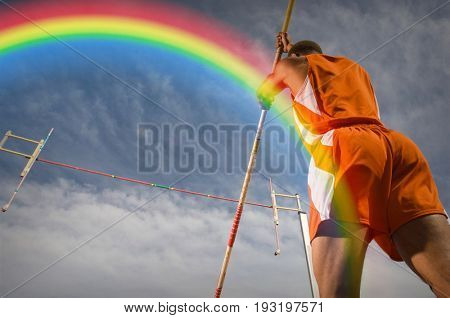 Pole-vaulter preparing for jump with rainbow in background