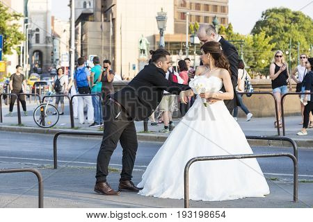 BUDAPEST, HUNGARY. 23 JUNE, 2017: A group of wedding photographers on the streets of Budapest is holding a photo session for a couple of newlyweds.
