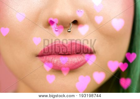 Lips of young woman wearing pink lipstick with heart background