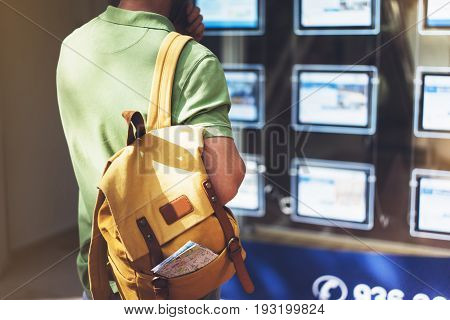 Hipster man with backpack and map looking ad promo poster hotel choose apartments. Tourist traveler planning route on background advert hostel city. Person hiker select hotel backdrop summer street