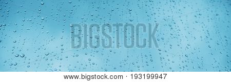 Blue glass with raindrops background texture horizontal top view isolated rain on the window backdrop light blue sky clear water on space blank back mockup nuture wall