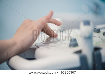 Skillful sonographer using ultrasound machine at work.