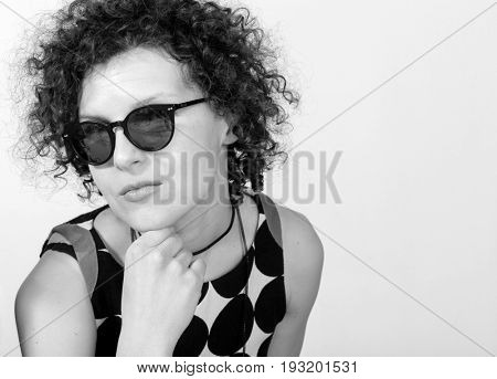 Girl with dark glasses and curly hair looks in camera. Portrait