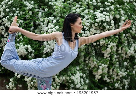 Portrait of beautiful woman in green leaves and blooming flowers doing yoga. Shallow depth of field