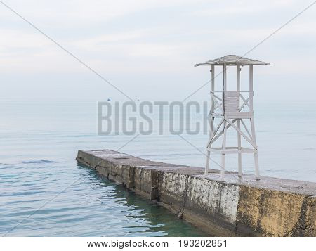 White wooden rescue tower on the breakwater. Seascape in soft blue tones