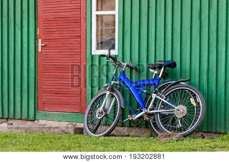 Old bicycles parked near a wood wall and doors