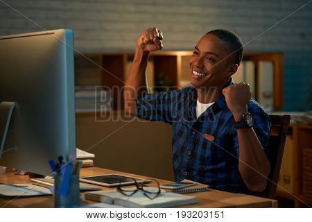 Joyful Afro-American businessman triumphing with raised hands while sitting in front of computer in modern open plan office, waist-up portrait