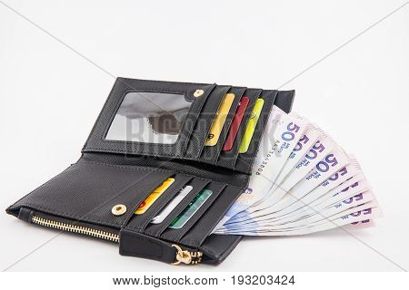 Black wallet filled with fifty thousand Colombian pesos bills