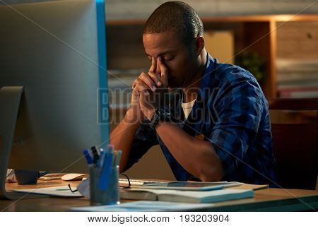 Tired young white collar worker rubbing his eyes while sitting in front of computer and working on promising project, blurred background